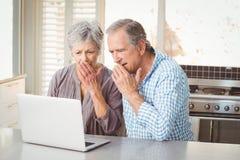 Couples supérieurs choqués regardant l'ordinateur portable Photographie stock
