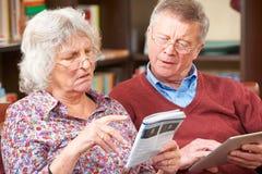 Couples supérieurs confus essayant d'actionner la Tablette de Digital images libres de droits