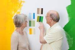 Couples supérieurs décidant d'une nouvelle couleur de peinture photos libres de droits