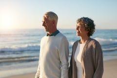 Couples supérieurs décontractés marchant sur la plage Photo stock