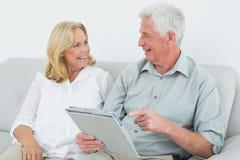 Couples supérieurs décontractés utilisant le comprimé numérique à la maison Images stock