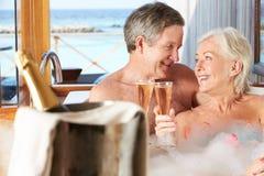 Couples supérieurs détendant à Bath buvant Champagne Together Photos libres de droits