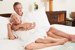 Couples supérieurs détendant dans des robes longues de port de chambre d'hôtel image stock