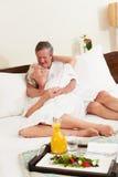 Couples supérieurs détendant dans des robes longues de port de chambre d'hôtel Photos stock