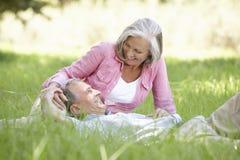 Couples supérieurs détendant en Sunny Summer Field Photographie stock libre de droits