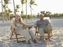 Couples supérieurs détendant sur des chaises longues à la plage Images libres de droits