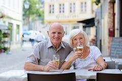 Couples supérieurs détendant sur le café d'extérieur Photographie stock