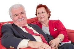 Couples supérieurs dévoués posés sur un sofa rouge Image libre de droits