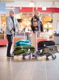 Couples supérieurs d'affaires marchant avec le bagage dans des chariots chez Airpo photos libres de droits