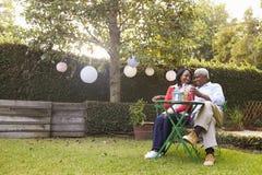 Couples supérieurs d'Afro-américain se reposant dans leur jardin arrière Photo stock