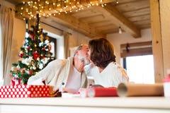 Couples supérieurs dans des chandails enveloppant des cadeaux de Noël ensemble Photos stock
