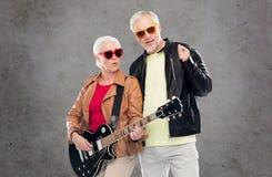 Couples supérieurs dans des lunettes de soleil avec la guitare électrique Image libre de droits