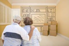 Couples supérieurs dans la chambre vide avec le dessin d'étagère sur le mur Photographie stock