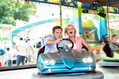 Couples supérieurs dans la voiture de butoir à la foire d'amusement Images libres de droits