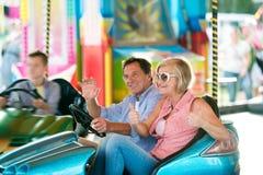 Couples supérieurs dans la voiture de butoir à la foire d'amusement Image stock