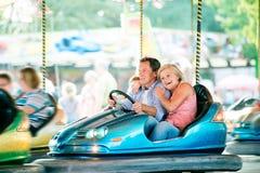Couples supérieurs dans la voiture de butoir à la foire d'amusement Photo stock