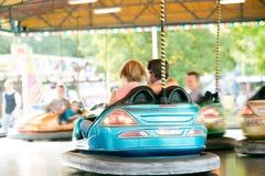 Couples supérieurs dans la voiture de butoir à la foire d'amusement Images stock