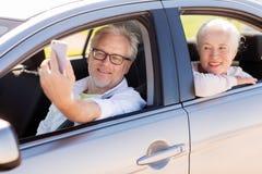 Couples supérieurs dans la voiture prenant le selfie de smartphone Photos libres de droits