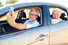 Couples supérieurs dans la voiture prenant le selfie de smartphone Photo stock