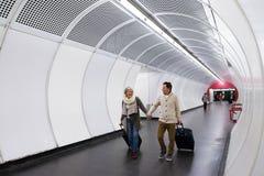 Couples supérieurs dans le couloir du souterrain tirant le bagage de chariot Photos stock