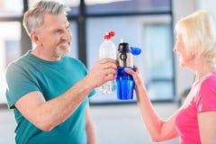 Couples supérieurs de forme physique tenant des bouteilles avec le gymnase de l'eau Photographie stock