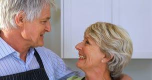 Couples supérieurs de sourire agissant l'un sur l'autre les uns avec les autres dans la cuisine clips vidéos