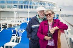 Couples supérieurs de sourire appréciant la plate-forme d'un bateau de croisière Photographie stock