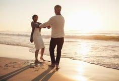Couples supérieurs de sourire ayant l'amusement sur la plage Photo libre de droits