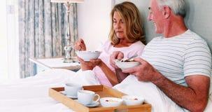 Couples supérieurs de sourire prenant le petit déjeuner sur le lit banque de vidéos