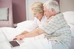 Couples supérieurs de sourire riant tout en à l'aide de l'ordinateur portable Photo stock