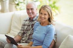 Couples supérieurs de sourire se reposant sur le sofa avec le comprimé numérique dans le salon Image libre de droits