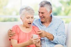 Couples supérieurs de sourire utilisant le smartphone image stock