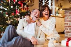 Couples supérieurs devant l'arbre de Noël avec des présents Photos stock