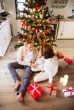 Couples supérieurs devant les andouillers de port de cerfs communs d'arbre de Noël Image libre de droits