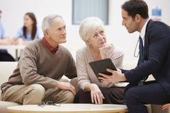 Couples supérieurs discutant des résultats d'essai avec le docteur Image stock