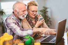 Couples supérieurs enthousiastes regardant un ordinateur portable ensemble image stock