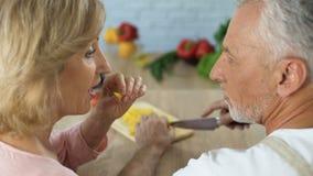 Couples supérieurs espiègles faisant cuire le dîner végétal à la maison, unité de famille clips vidéos
