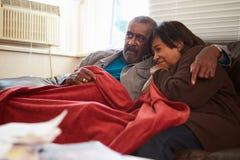 Couples supérieurs essayant de garder la couverture de dessous chaude à la maison Photographie stock libre de droits