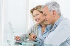 Couples supérieurs faisant des emplettes en ligne Photographie stock libre de droits