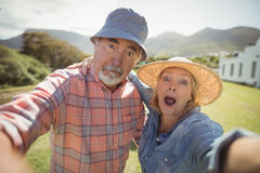 Couples supérieurs faisant l'expression du visage dans le jardin Image stock