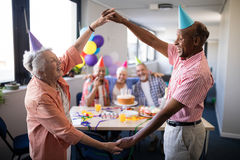 Couples supérieurs faisant le cadre contre des amis à la fête d'anniversaire Photographie stock libre de droits
