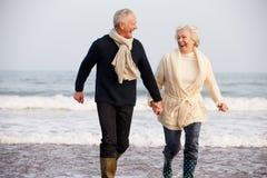 Couples supérieurs fonctionnant le long de la plage d'hiver Images stock