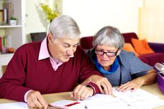 Couples supérieurs heureux à la maison calculant la dette photographie stock libre de droits