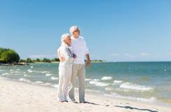 Couples supérieurs heureux étreignant sur la plage d'été Photos stock