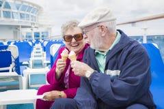 Couples supérieurs heureux appréciant la crème glacée sur la plate-forme du bateau de croisière Photos stock