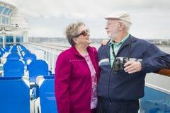 Couples supérieurs heureux appréciant la plate-forme d'un bateau de croisière Images stock