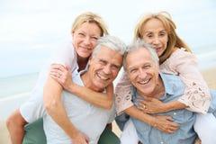 Couples supérieurs heureux appréciant sur la plage Photo libre de droits