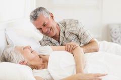 Couples supérieurs heureux au lit image stock
