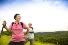 Couples supérieurs heureux augmentant sur la montagne Photographie stock libre de droits