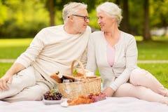 Couples supérieurs heureux ayant le pique-nique au parc d'été Image libre de droits